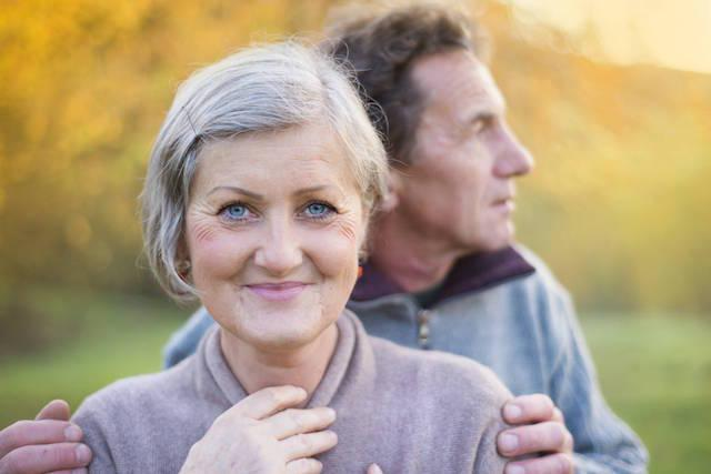 older woman smiling with husband behind her looking off into distance