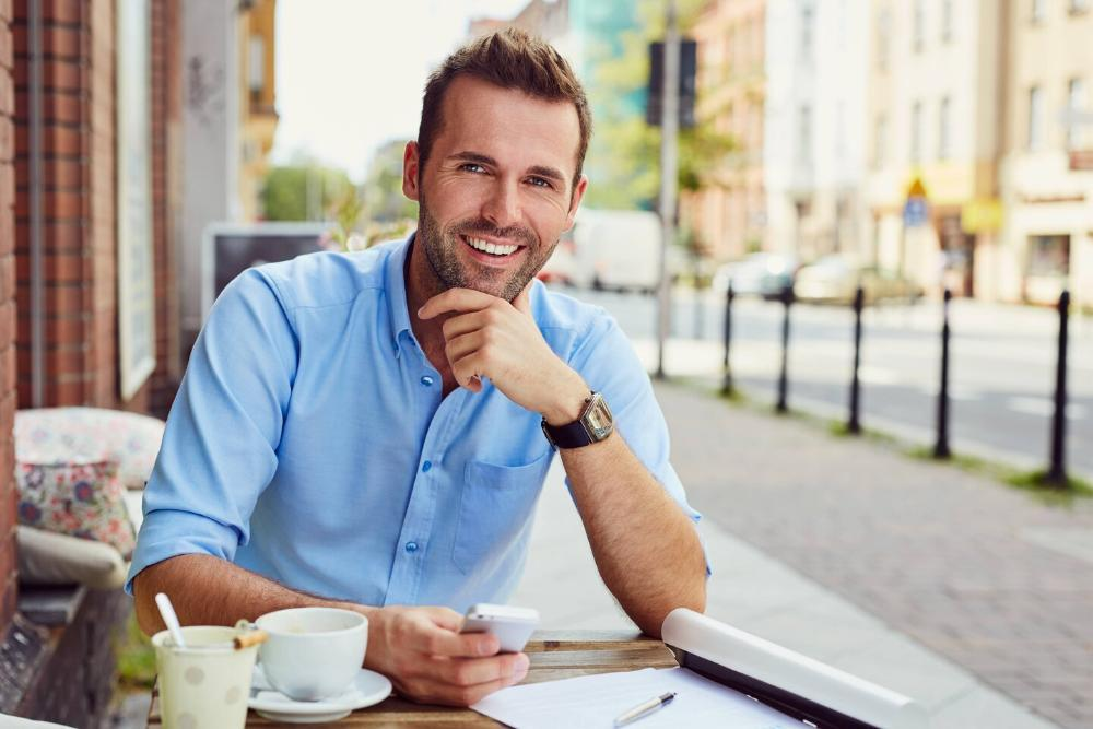 man smiling while sitting at cafe table